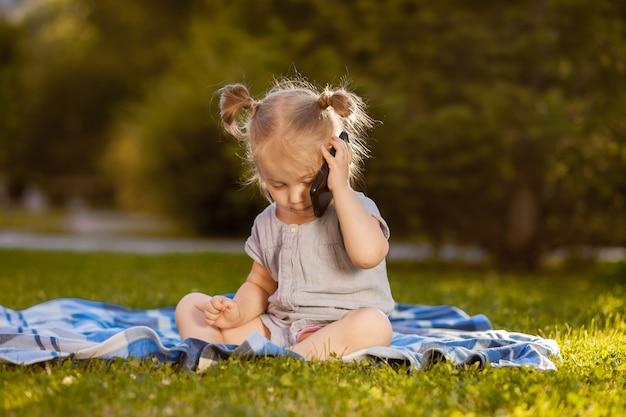 Kind praten op een mobiele telefoon in het park