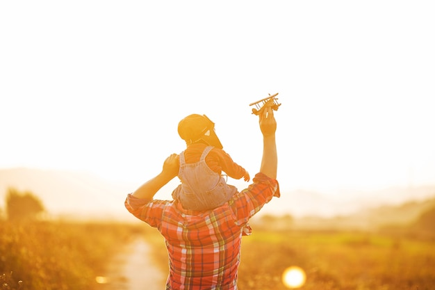 Kind proefvlieger met vliegtuigdromen van het reizen in de zomer in aard bij zonsondergang,