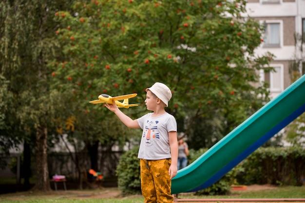Kind proefvlieger met vliegtuigdromen van het reizen in de zomer in aard bij zonsondergang
