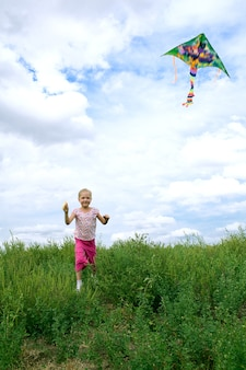 Kind rennen op veld met vlieger