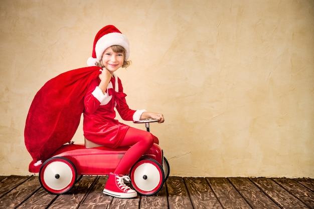 Kind rijden in rode auto. kind bedrijf kerst tas. kerst vakantie concept