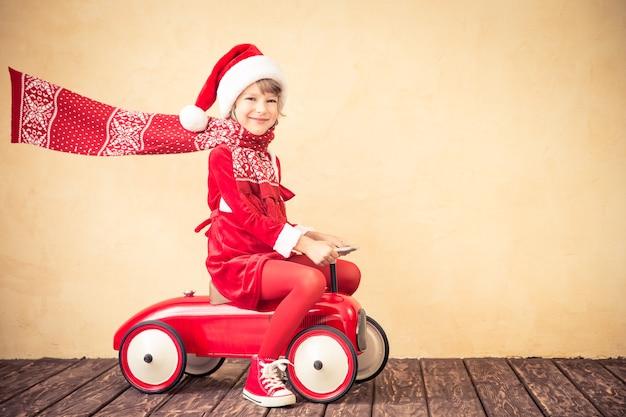 Kind rijden in rode kerst auto. kerst vakantie concept