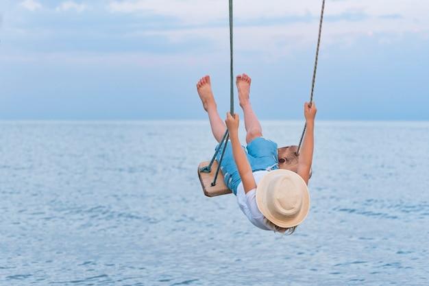 Kind rijdt op touw zwaait over het water en tilde hoge benen op. vakantie aan zee.