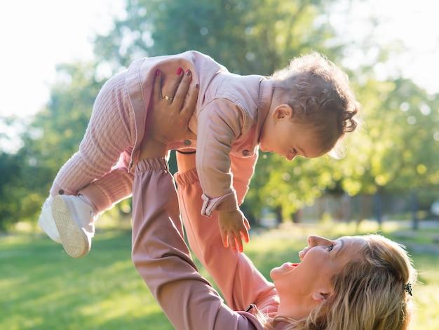 Kind roze kleding dragen en moeder die haar houden