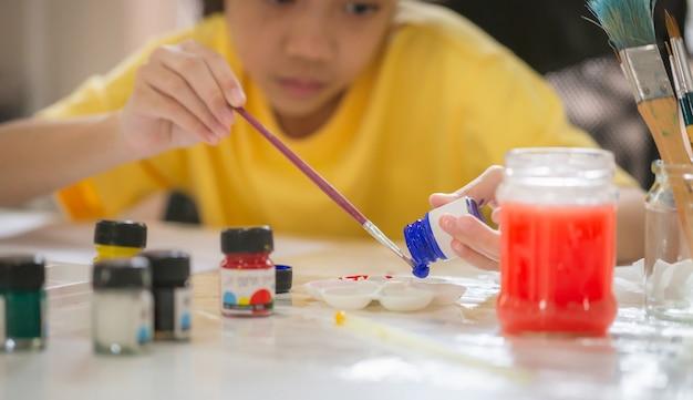 Kind schilderen aan tafel in speelkamer, meisje met penseel en palet schilderen, online schilderen leren