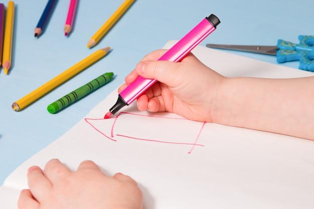 Kind schildert een huis in een album, kopieer plaats, blauwe achtergrondactiviteiten voor kinderen