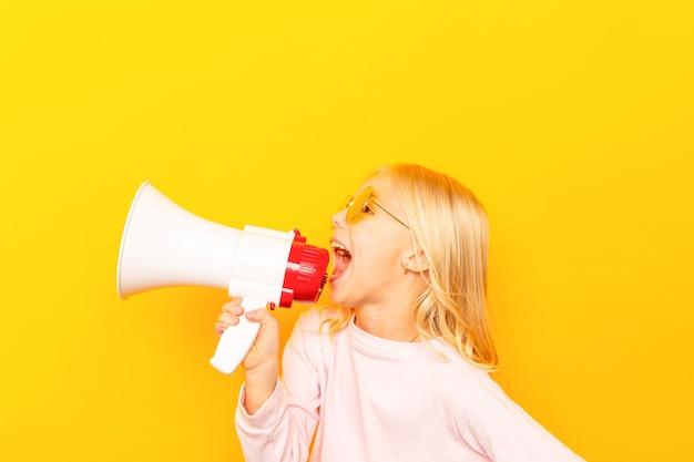 Kind schreeuwen door vintage megafoon. communicatie concept. blauwe hemelachtergrond als exemplaarruimte voor uw tekst.