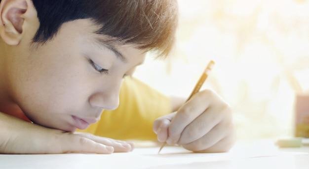 Kind schrijft huiswerk. kinderen die thuis werken, werken op de tafel in de woonkamer
