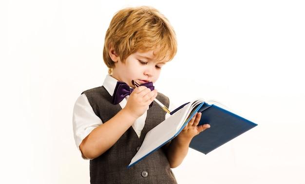 Kind schrijven in notitieblok. schooljongen in schooluniform. terug naar school.