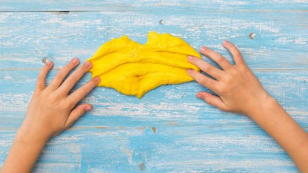 Kind slijm gele uitstrijkjes op de houten tafel. antistress voor speelgoed. speelgoed voor de ontwikkeling van handmotoriek.