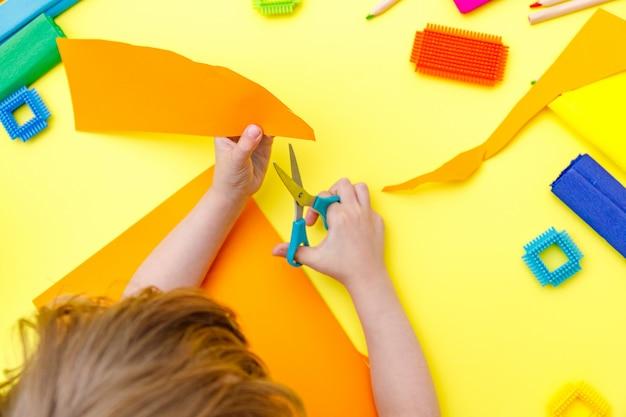 Kind snijden gekleurd oranje papier met een schaar op een tafel voor wat knutselen