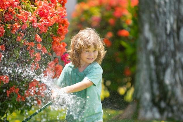 Kind speelt in de tuin, giet uit de slang, maakt regen. gelukkig kindertijdconcept. kind dat water op de bomen giet. kinderverzorging voor de planten in de achtertuin.