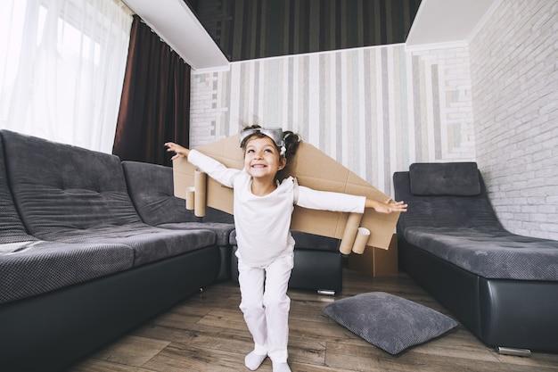 Kind speelt in het kostuum van de piloot en wil in de lucht vliegen Premium Foto