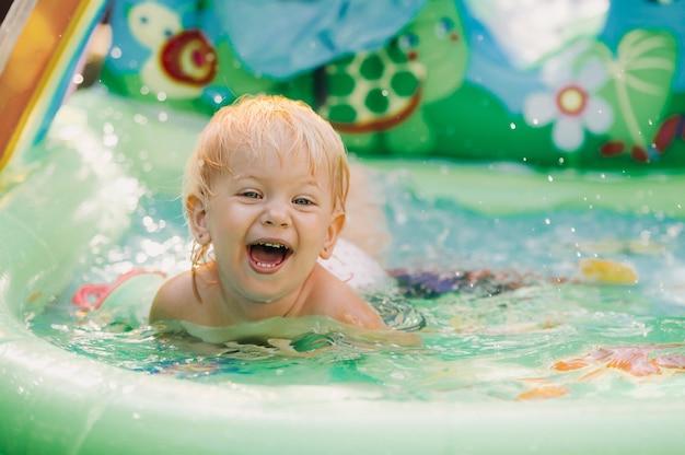 Kind speelt in het zwembad. klein meisje in het zwembad, glimlachend kind.