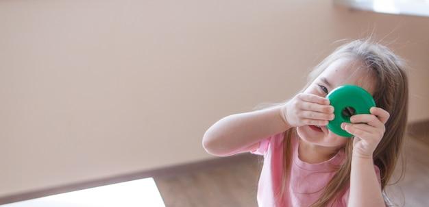 Kind speelt met detail van piramide. meisje kijkt door gat in het wiel. concept van de ontwikkeling van motorische vaardigheden, educatieve spelletjes, kindertijd, kinderdag, kleuterschool, huisarrest copyspace