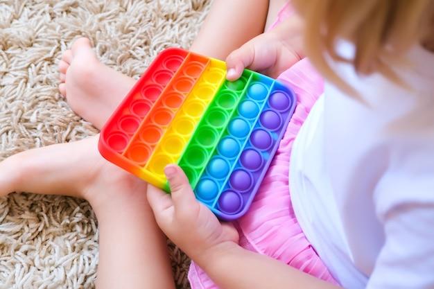 Kind speelt met een fladderende fidget. populair flexibel zintuiglijk speelgoed voor kinderen ontwikkelt fijne motoriek, antistress, kan worden gebruikt voor training met autistische mensen, popit-speelgoed