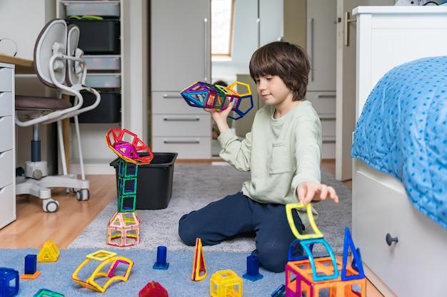Kind speelt met een magnetische constructeur in zijn slaapkamer