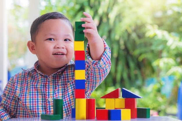 Kind speelt met houten kleurrijke blokken kleine jongen is van plan toren te bouwen door houten kleurrijke blok educatief speelgoed en thuis leren kinderen concept