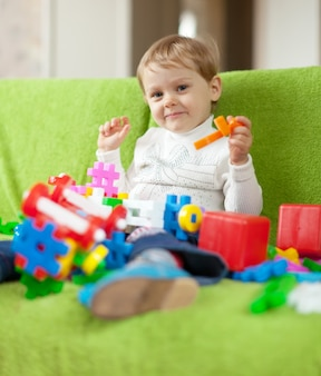 Kind speelt met speelgoed in huis