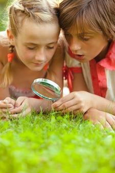 Kind speelt met vergrootglas in de tuin