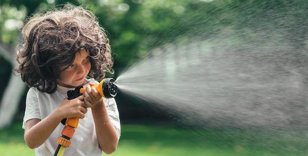 Kind speelt met water in de achtertuin in de tuin