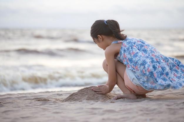 Kind speelt met zand op het strand klein meisje speelt 's avonds buiten
