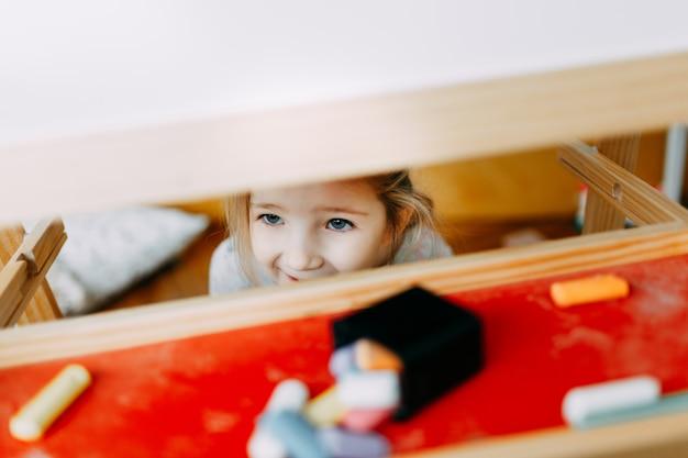 Kind speelt verstoppertje. het kind verborg zich achter de tekentafel in de kinderkamer. zichtbaar alleen blij gezicht