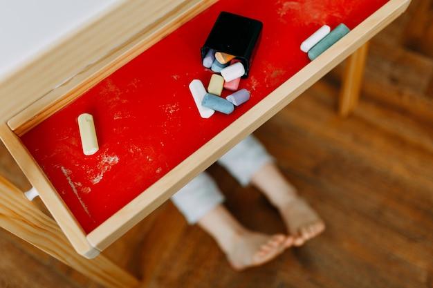 Kind speelt verstoppertje. het kind verborg zich achter de tekentafel in de kinderkamer. zichtbare alleen blote voeten