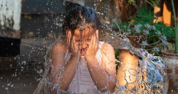 Kind spelen in de tuin met water in de braziliaanse zomer