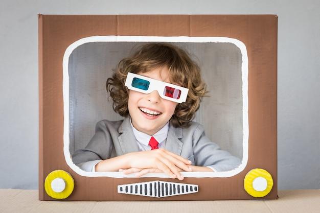 Kind spelen met kartonnen doos tv. kind plezier thuis. video bloggen concept