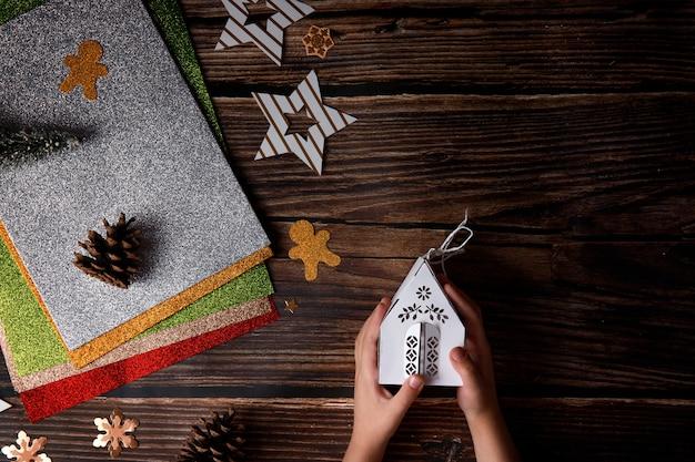 Kind spelen met kerst ambachten op houten achtergrond. vakantieartikelen op een tafel.