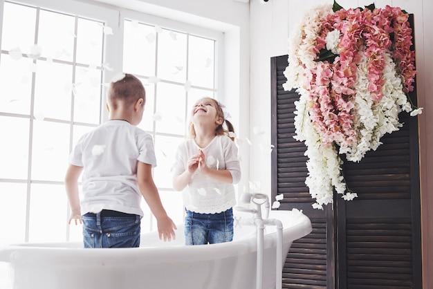 Kind spelen met rozenblaadjes in huis badkamer. klein meisje en jongen fawing plezier en vreugde samen. kindertijd en de realisatie van dromen, fantasie, verbeelding