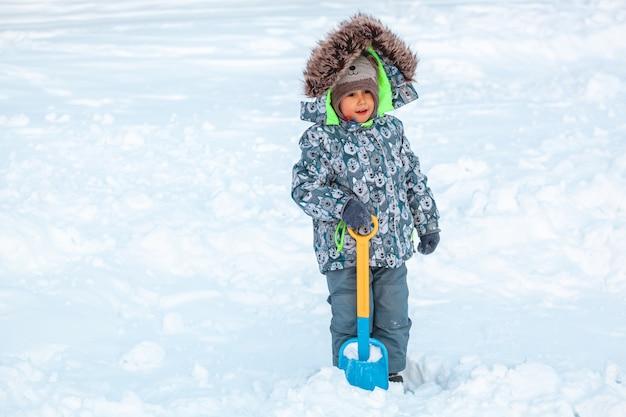 Kind spelen met schop in de sneeuw op een zonnige winterdag
