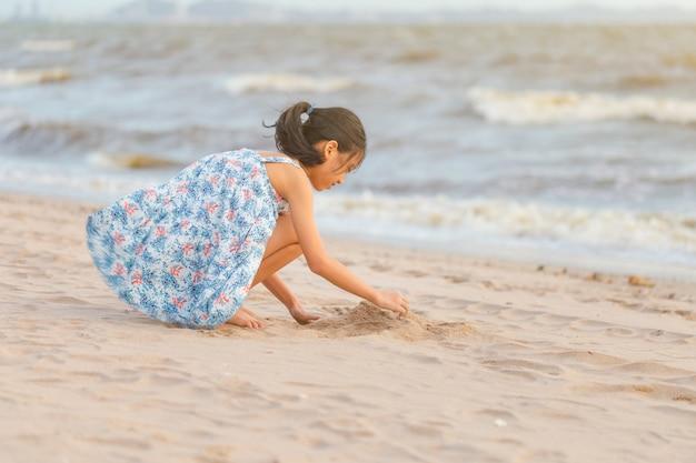 Kind spelen met zand op het strand, klein meisje spelen buiten zonsondergang avondtijd Premium Foto