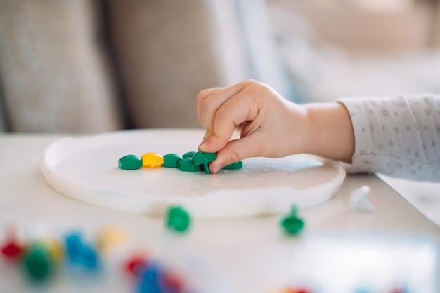 Kind spelen mozaïek op tafel close-up.
