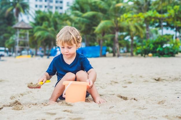 Kind spelen op het strand met een schop en een emmer