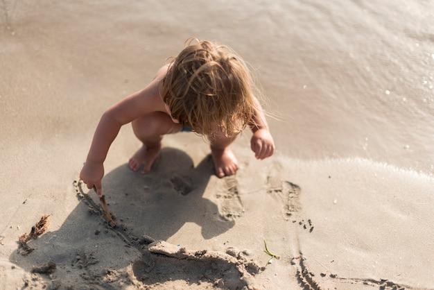 Kind spelen op het strand van bovenaf
