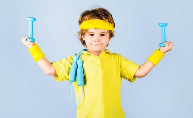 Kind sportman. fitness voor kinderen. jongen in sportkleding met springtouw en halters.