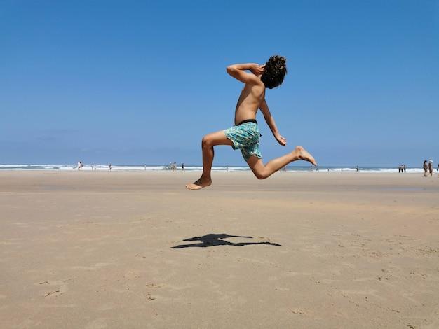Kind springt opgewonden op het strand