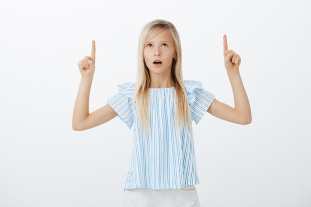 Kind staat nog steeds verbaasd over bijenkorf. geschokt en verwonderd schattig vrouwelijk kind in blauwe blouse, handen opstekend, wijzend en opzoeken met geïnteresseerde en nieuwsgierige uitdrukking over grijze muur