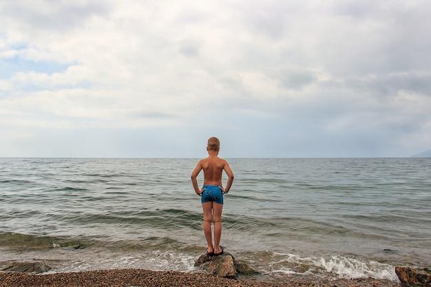 Kind staat op een steen aan de oever van het meer.