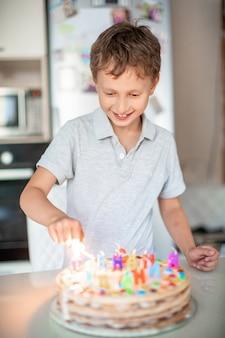 Kind steekt kaarsen op een verjaardagstaart. verjaardag thuis. europese