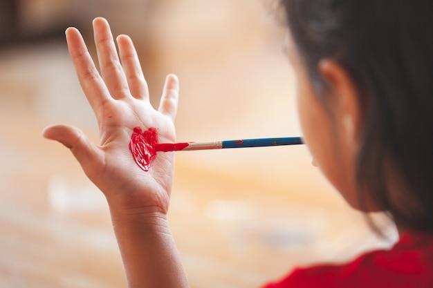 Kind tekenen en schilderen van een hart op haar hand met plezier