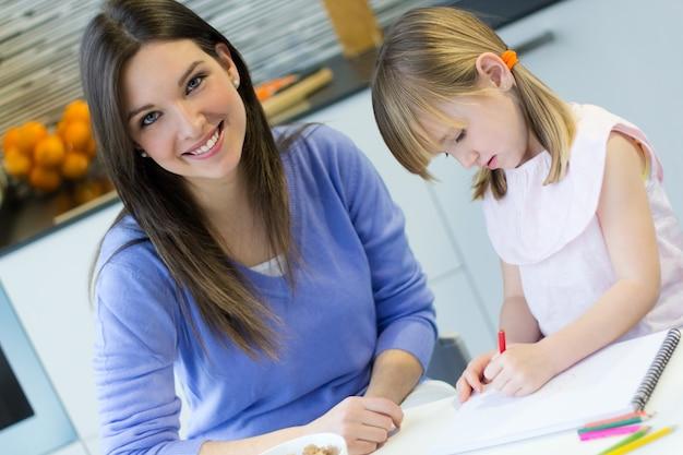 Kind tekenen met krijtjes met haar moeder thuis