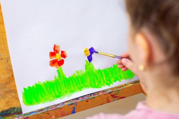 Kind tekent bloemen door aquarellen op wit papier op een ezel. kinder en aarde dag concept.
