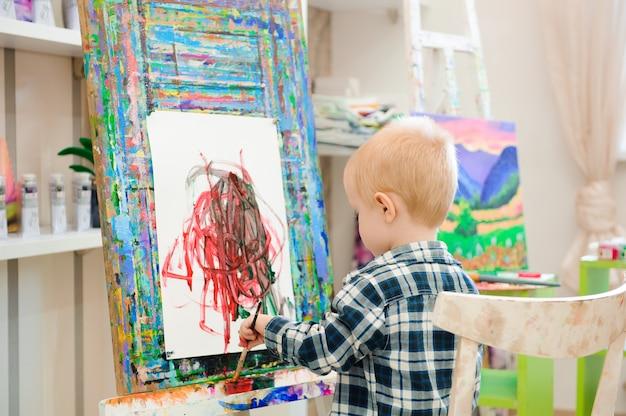 Kind tekent een foto schildert op kunstles