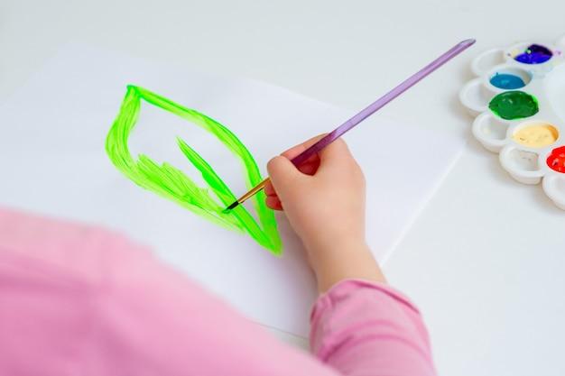 Kind tekent groen blad