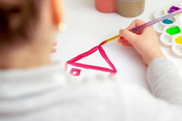 Kind tekent het dak van het huis met aquarellen op wit papier.