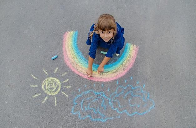 Kind tekent met krijt op de stoep
