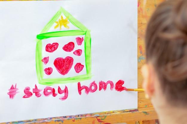 Kind tekent woorden stay home onder groen huis met rode harten op wit papier op ezel. blijf thuis-concept.